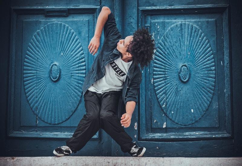 Tancerz na tle niebieskich drzwi.